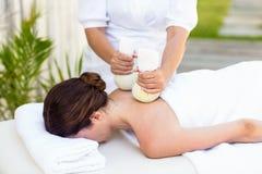 Brune ayant le massage avec les compresses de fines herbes Photographie stock libre de droits