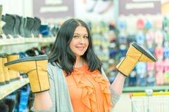Brune caucasienne assez jeune de femme souriant et choisissant des chaussures d'hiver dans le magasin Bottes sur ses mains Concep images stock