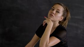 Brune caucasienne dans les vêtements de sport posant sur la caméra, fond noir banque de vidéos
