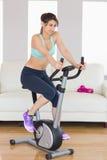 Brune convenable établissant sur le vélo d'exercice Photographie stock libre de droits