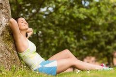 Brune convenable de sourire se reposant et détendant contre un arbre Image libre de droits