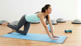 Brune convenable faisant des pilates sur le tapis d'exercice clips vidéos