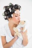 Brune dans des rouleaux de cheveux embrassant le nounours de moutons Image libre de droits
