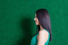 Brune dans la robe verte contre le mur Photographie stock libre de droits