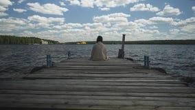 Brune dans la séance triste de plaid sur un vieux pilier en bois et regards à l'eau et à la forêt dans la distance banque de vidéos