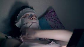Brune dans le masque spécial de feuille de difficultés supérieures roses sur le visage banque de vidéos