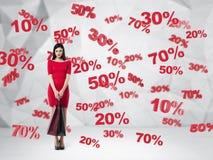 Brune dans une robe rouge avec les paniers Symboles de remise et de vente : 10% 20% 30% 50% 70% Fond contemporain Photos libres de droits