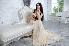 Brune de attirance détendant sur le sofa dans l'intérieur de luxe Photographie stock libre de droits