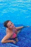 Brune de beauté dans la piscine tropicale Photographie stock libre de droits