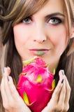 Brune de Headshot, regard mystique foncé et rouge à lèvres vert, supportant le fruit rose de pitaya avec les deux mains faisant f Photos stock