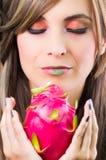 Brune de Headshot, regard mystique foncé et rouge à lèvres vert, supportant le fruit rose de pitaya avec les deux mains faisant f Image stock