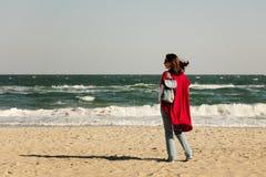 Brune de jeune femme dans un cardigan rouge et des jeans bleu-clair, W Photographie stock libre de droits