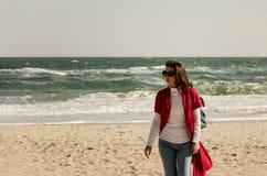 Brune de jeune femme dans un cardigan rouge et des jeans bleu-clair, W Photos libres de droits