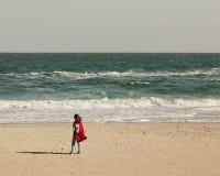 Brune de jeune femme dans un cardigan rouge et des jeans bleu-clair, W Photos stock