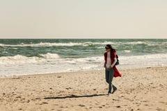 Brune de jeune femme dans un cardigan rouge et des jeans bleu-clair, W Images libres de droits
