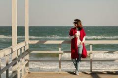 Brune de jeune femme dans un cardigan rouge et un wa bleu-clair de jeans Photographie stock