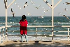 Brune de jeune femme dans un cardigan rouge et un wa bleu-clair de jeans Photo libre de droits