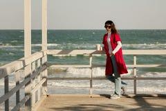 Brune de jeune femme dans un cardigan rouge et un wa bleu-clair de jeans Images libres de droits