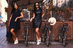 Brune deux sexy portant les robes noires élégantes, posant près des bicyclettes sur un fond d'un café Images libres de droits