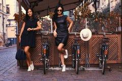 Brune deux sexy portant les robes noires élégantes, posant près des bicyclettes sur un fond d'un café Photos stock