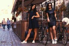 Brune deux sexy portant les robes noires élégantes, posant près des bicyclettes sur un fond d'un café Image libre de droits