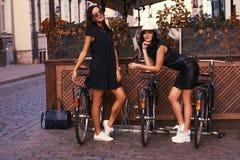 Brune deux sexy portant les robes noires élégantes, posant près des bicyclettes sur un fond d'un café Photo stock