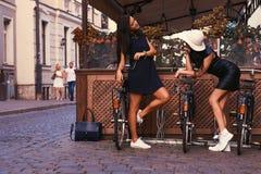 Brune deux sexy portant les robes noires élégantes, posant près des bicyclettes sur un fond d'un café Photo libre de droits