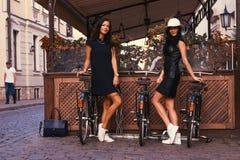 Brune deux sexy portant les robes noires élégantes, posant près des bicyclettes sur un fond d'un café Photographie stock libre de droits