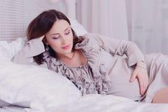 Brune enceinte de jeunes se situant dans la chambre à coucher et tenant son ventre Photo libre de droits