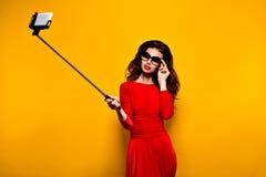 Brune faisant le selfie dans les lunettes de soleil et la robe rouge Photos stock
