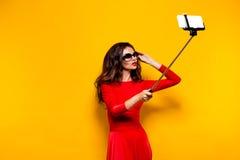 Brune faisant le selfie dans les lunettes de soleil et la robe rouge Photo libre de droits