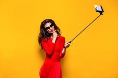 Brune faisant le selfie dans les lunettes de soleil et la robe rouge Images stock