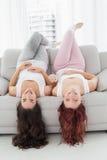Brune gaie et mensonge roux sur le sofa dans le salon Photographie stock libre de droits