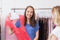 Brune heureuse montrant une robe rouge Photo libre de droits