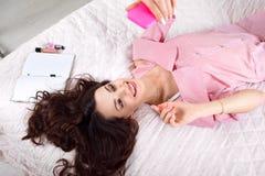 Brune joyeuse faisant le selfie se trouvant sur le lit image libre de droits