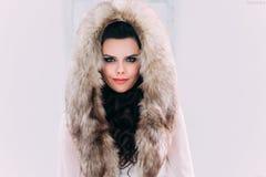 Brune luxueuse dans un manteau de fourrure Photographie stock
