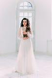 Brune luxueuse dans une robe blanche Photos stock