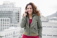 Brune magnifique de sourire dans téléphoner de mode d'hiver Image stock