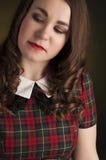 Brune mignonne dans la robe de tartan avec les lèvres et les curles rouges Portrait de studio Photographie stock