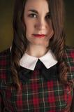 Brune mignonne dans la robe de tartan avec les lèvres et les curles rouges Portrait de studio Image stock