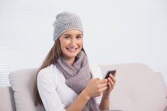 Brune mignonne de sourire avec le chapeau d'hiver sur utiliser son smartphone Photographie stock libre de droits
