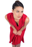 Brune mystérieuse songeuse dans la pose rouge de robe Photographie stock libre de droits