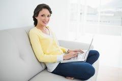Brune occasionnelle attrayante dans le cardigan jaune utilisant un ordinateur portable photographie stock