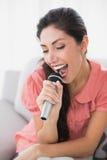 Brune se reposant sur son sofa chantant dans le microphone Photos libres de droits
