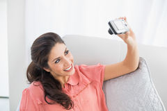 Brune se reposant sur son sofa prenant une photo d'elle-même Images libres de droits