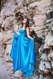 Brune sexy à côté d'une roche en pierre dans une robe bleue Photo libre de droits