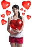 Brune sexy avec le ballon en forme de coeur devant l'appareil-photo Photographie stock