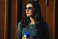 Brune sexy et jolie dans des lunettes de soleil avec du café à disposition Images stock