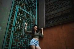 Brune sexy et jolie en bref posant sur les rues Photographie stock libre de droits