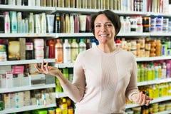 Brune sélectionnant la bouteille de shampooing Photos stock